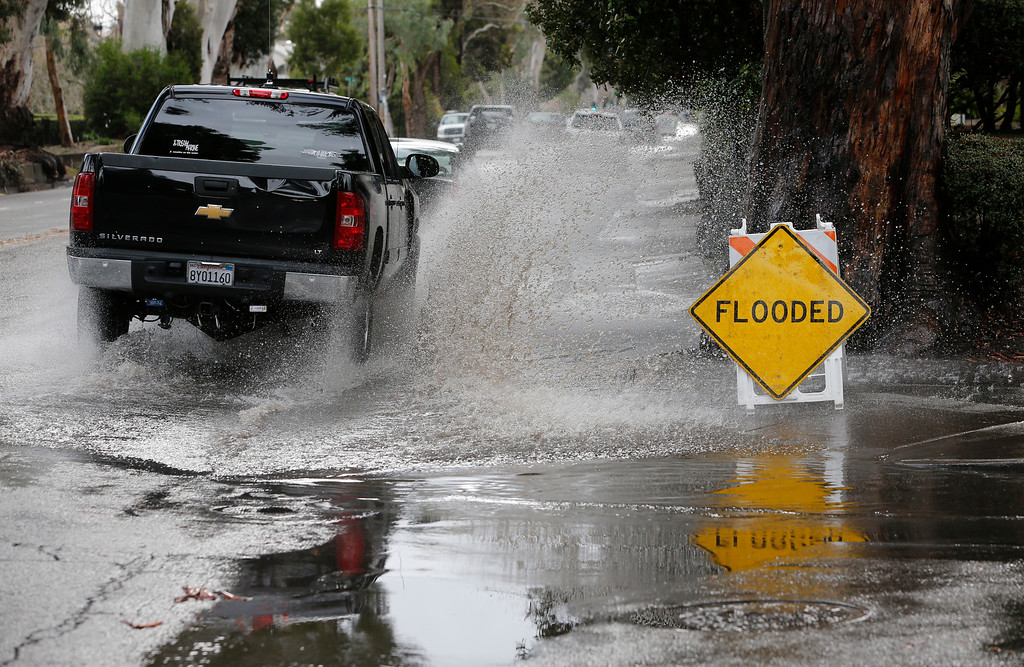 . Cars drive through flooded intersections on El Camino Real in Burlingame,  Calif., on Friday, Feb. 28, 2014. (John Green/Bay Area News Group)