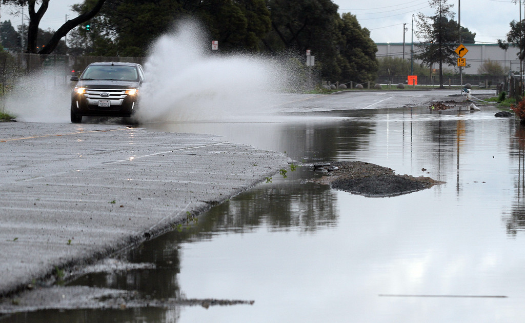 . Commuters using the frontage road, Oakport Street, in Oakland, Calif., drive through some large puddles on Friday, Feb. 28, 2014.  (Laura A. Oda/Bay Area News Group)