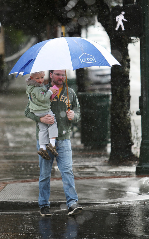 . Mike Kennedy, of Los Gatos, carries his son, Colin Kennedy, 3, as the rain comes down in Los Gatos, Calif. on Friday, Feb. 28, 2014. (Jim Gensheimer/Bay Area News Group)