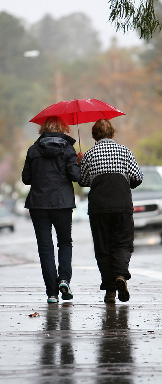 . Sharing an umbrella in the rain, Nancy Jobe, left, and Claudia Dalziel, both of Los Gatos, walk to their vehicle after getting coffee in Los Gatos, Calif. on Friday, Feb. 28, 2014. (Jim Gensheimer/Bay Area News Group)