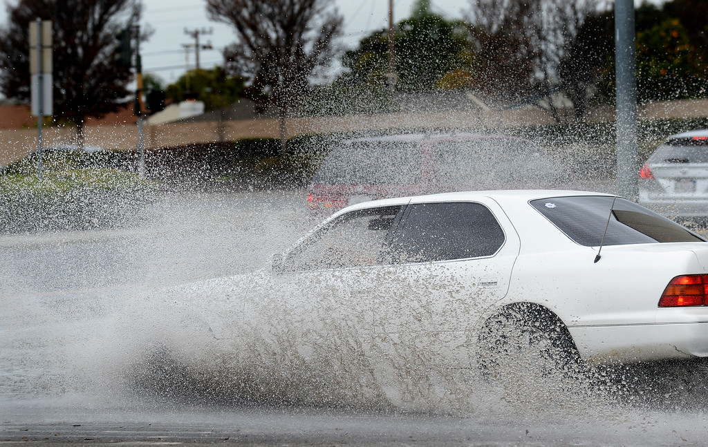 . A motorist drives through standing water on Southland Drive in Hayward, Calif., on Friday, Feb. 28, 2014. Heavy rain in the early morning caused flooding in many areas around the Bay Area and left standing water on many roadways. (Dan Honda/Bay Area News Group)