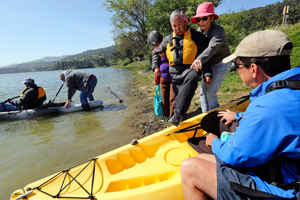 . Rob Knoles, one of the four coordinators of the Heroes on the Water program, right, steadies the kayak as Albert Anub prepares to get into the boat with the help of Physical Therapist Elizabeth McBride at the San Pablo Dam Reservoir Recreation Area on Friday, April 29, 2016.  Anub is a Vietnam veteran who is suffering from Parkinsons.  (Laura A. Oda/Bay Area News Group)