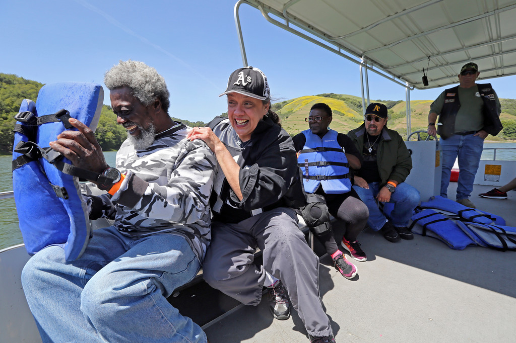. Jimmy Foster of Pittsburg, left, shields himself from the water spray as Michele Crow hides behind him as they join their fellow veterans Rita Jack and Grant Crow on a boat ride at the San Pablo Dam Reservoir Recreation Area on Friday, April 29, 2016 driven by Staff Sgt. Russ Roberts during the Heroes on the Water program. (Laura A. Oda/Bay Area News Group)