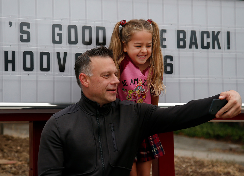 . Simone Garcia-Afshar takes a selfie with her father, Ramon Garcia, on her first day of school at Hoover Elementary school in Burlingame, Calif., Wednesday morning, Aug. 24, 2016. The school reopened today after having been shuttered for years. (Karl Mondon/Bay Area News Group)