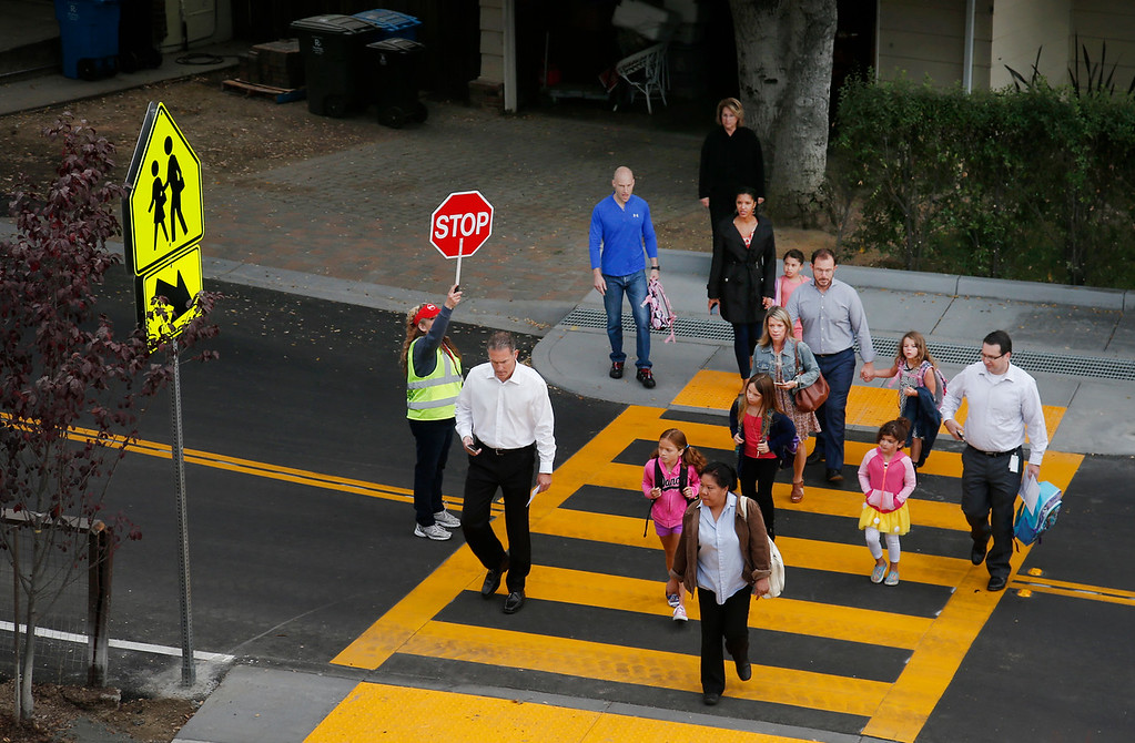 . Traffic guard Jennifer Orrante works the crosswalk on Summit Drive outside Hoover Elementary as it reopens for school for the first time in years in Burlingame, Calif., Wednesday morning, Aug. 24, 2016. (Karl Mondon/Bay Area News Group)