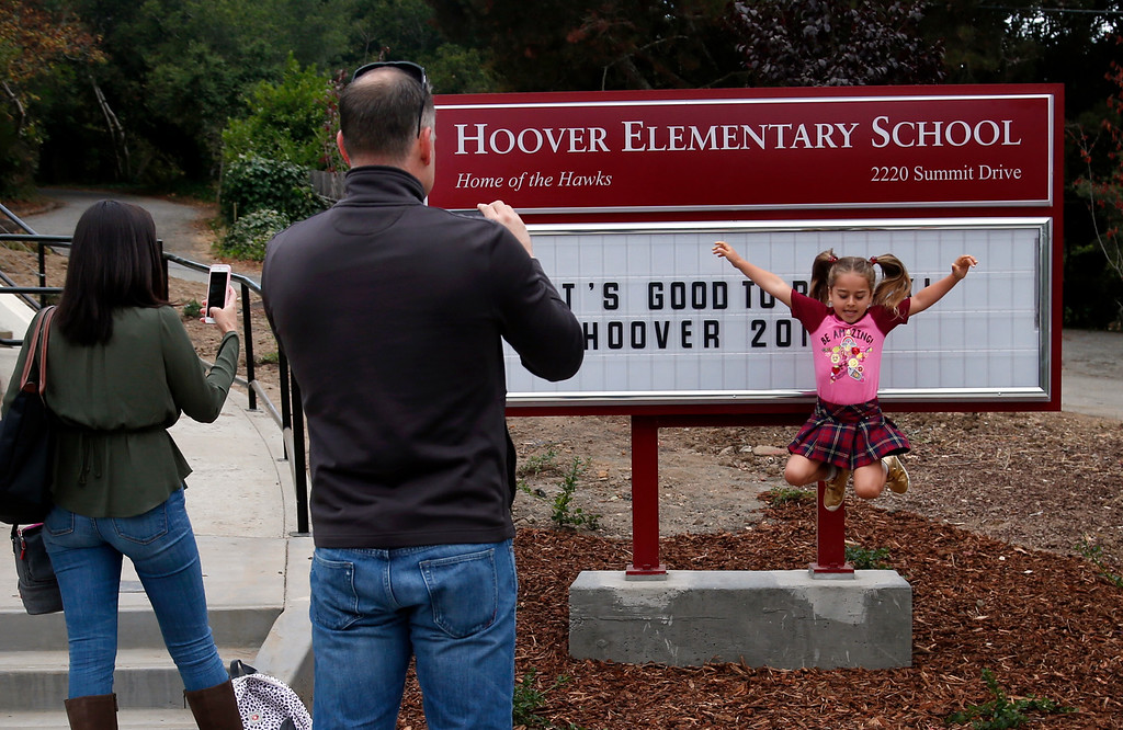 . Simone Garcia-Afshar jumps for the cameras of her parents Shireen Afshar and Ramon Garcia, on her first day of school at Hoover Elementary school in Burlingame, Calif., Wednesday morning, Aug. 24, 2016. The school reopened today after having been shuttered for years. (Karl Mondon/Bay Area News Group)