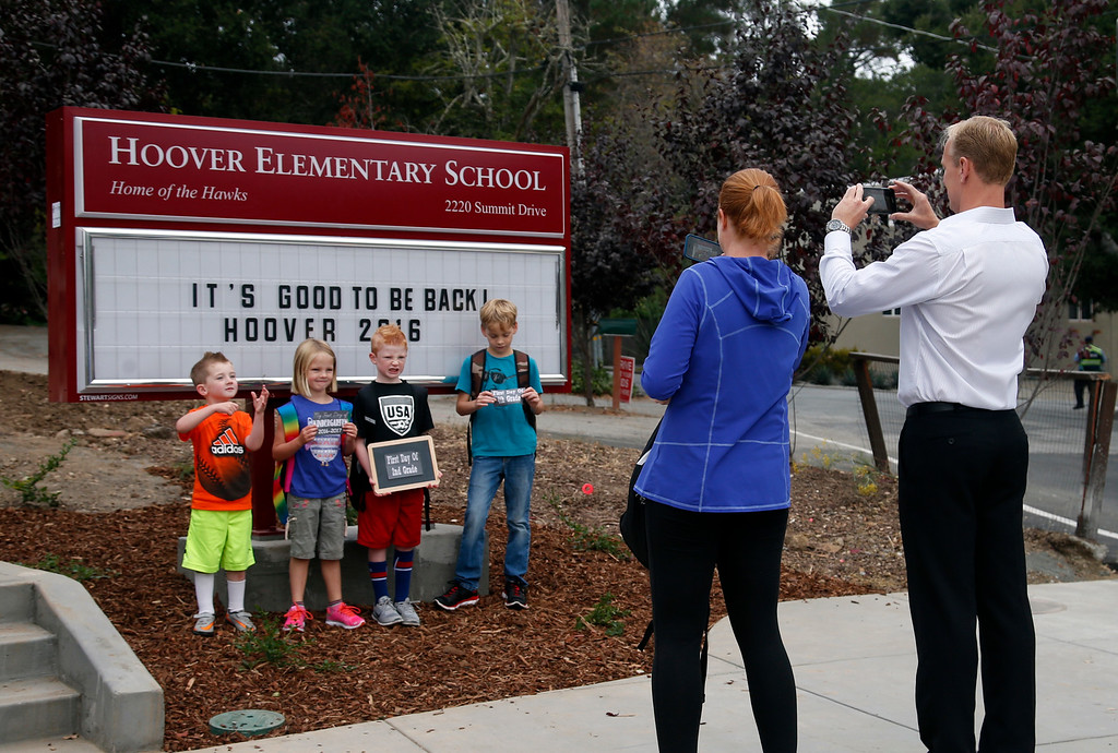 . Kathleen O\'Shea and her neighbor Grant Hay photograph their children on the first day of school at Hoover Elementary in Burlingame, Calif., Wednesday morning, Aug. 24, 2016. After being shuttered for many years, Hoover is being reopened. Kathleen was a 2nd grader at the school when it closed. Today she returns with her son Danny (third from left), as he enters 2nd grade. (Karl Mondon/Bay Area News Group)