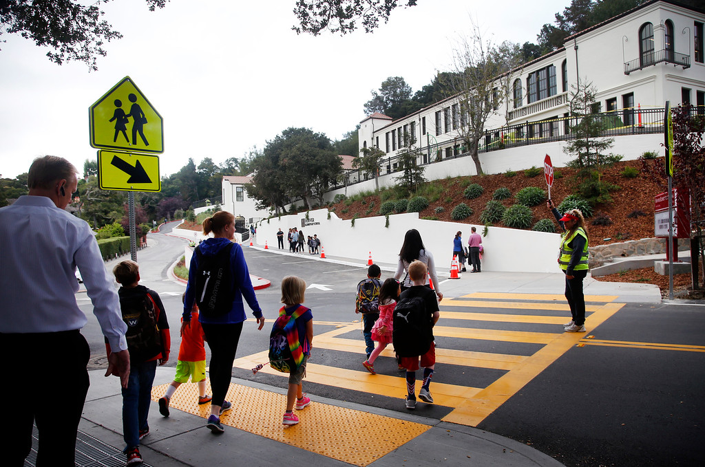 . Kathleen O\'Shea and her neighbor Grant Hay, left, walk their children to the first day of school at Hoover Elementary in Burlingame, Calif., Wednesday morning, Aug. 24, 2016. After being shuttered for many years, Hoover is being reopened. Kathleen was a 2nd grader at the school when it closed. Today she returns with her son Danny who is entering 2nd grade. (Karl Mondon/Bay Area News Group)