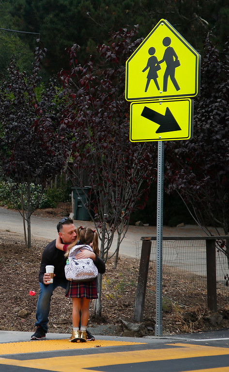 . Simone Garcia-Afshar gets a hug from her father, Ramon Garcia, on the first day of school at the re-opened Hoover Elementary school in Burlingame, Calif., Wednesday morning, Aug. 24, 2016. The school had been shuttered for years. (Karl Mondon/Bay Area News Group)