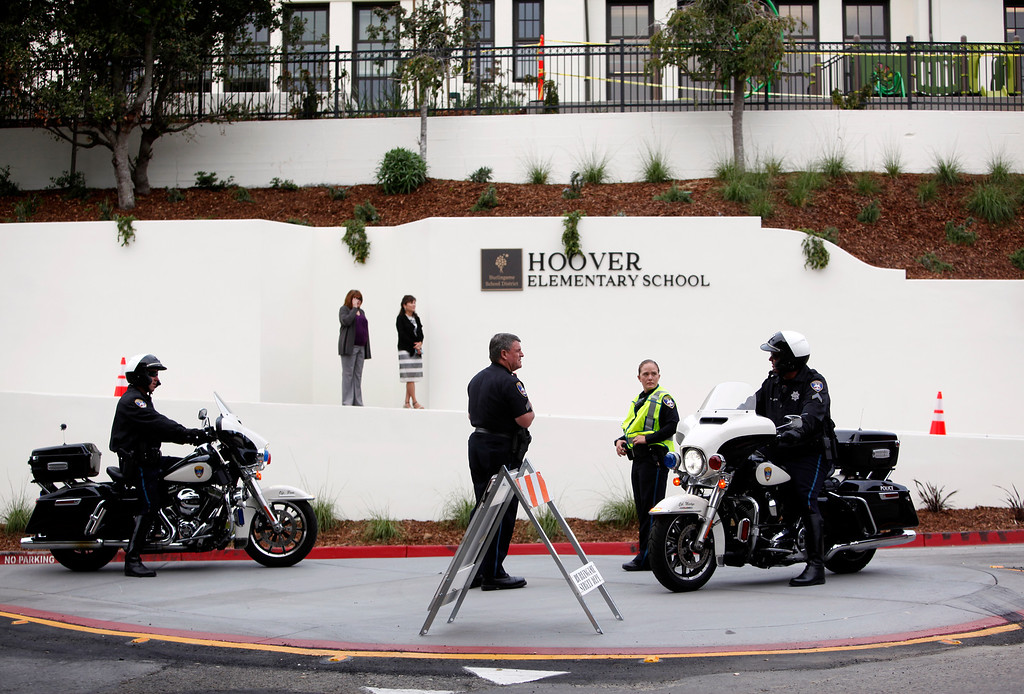 . Officials and police await the first day of school rush at  Hoover Elementary as it  reopens Wednesday morning, Aug. 24, 2016, for its first day of school in Burlingame, Calif., after being shuttered for years. (Karl Mondon/Bay Area News Group)