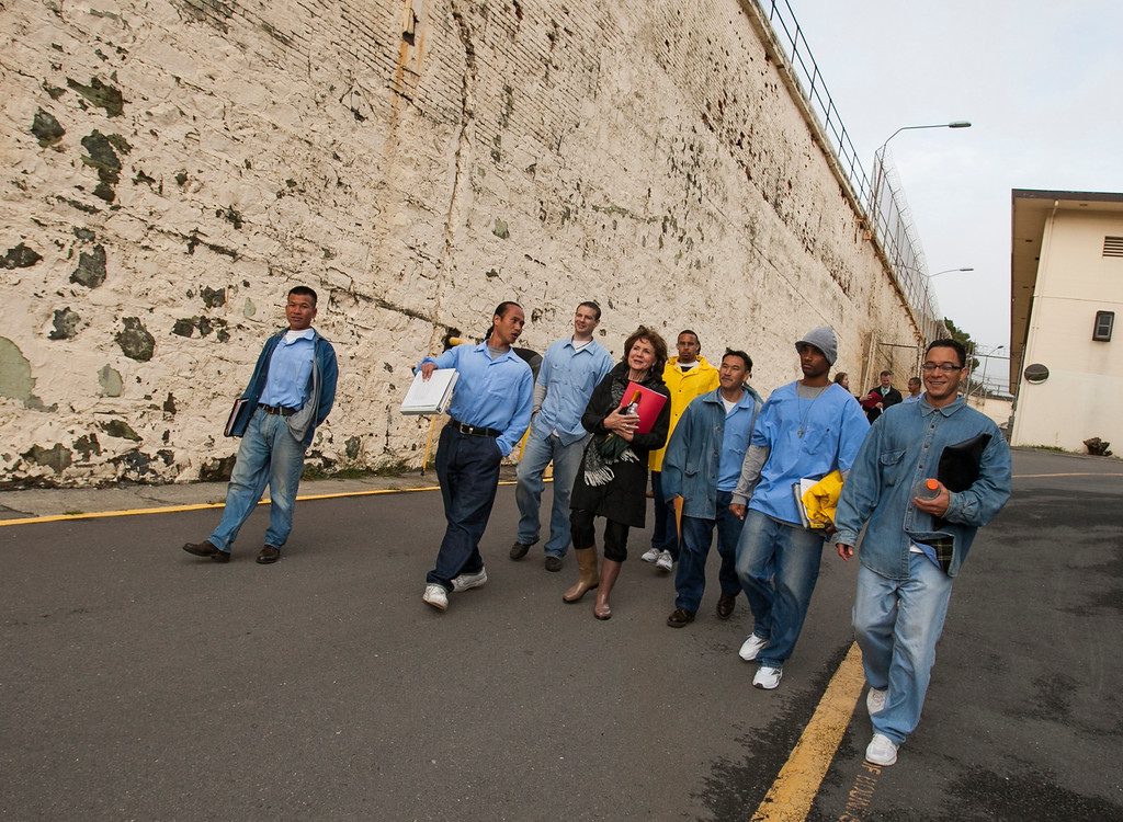 . Volunteer Gail Towle walks with members of Kid CAT to San Quentin\'s exercise yard, which includes basketball and tennis courts and a baseball diamond. (John Green/Bay Area News Group)