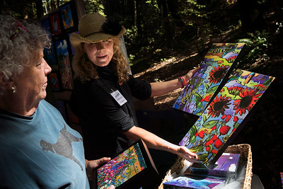 At center, artist Marna Schindler shows Jennifer Wisnom of Redwood city, some of her paintings during the King's Mountain Art Fair at the King's Mountain Firehouse in Woodside, Calif., on Monday, September 5, 2016. (LiPo Ching/Bay Area News Group)