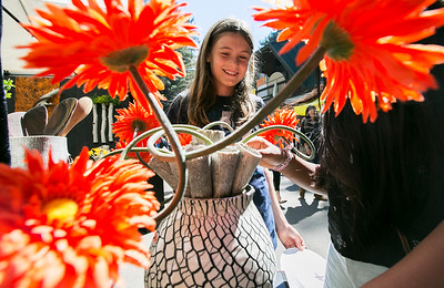 Kira Gosling, 10, likes the flowers in the pottery made by Erin Lunstrum Putsch at the King's Mountain Art Fair at the King's Mountain Firehouse in Woodside, Calif., on Monday, September 5, 2016. (LiPo Ching/Bay Area News Group)