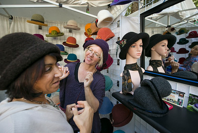 At center, hatmaker Tess McGuire helps Hope Levy of San Francisco try on a hat during the King's Mountain Art Fair at the King's Mountain Firehouse in Woodside, Calif., on Monday, September 5, 2016. (LiPo Ching/Bay Area News Group)