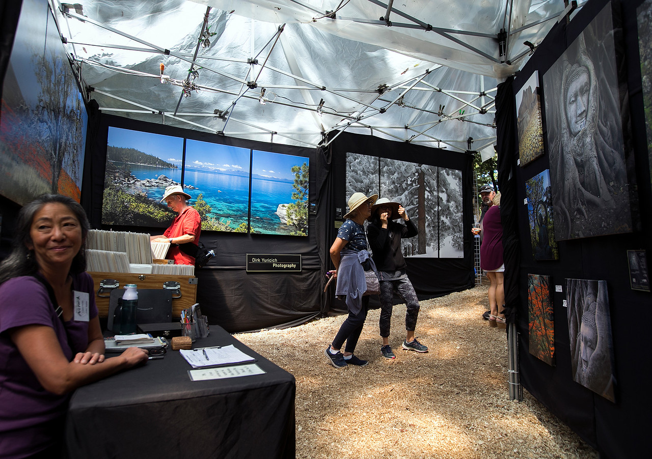 People walk through Dirk Yuricich Photography's booth during the King's Mountain Art Fair at the King's Mountain Firehouse in Woodside, Calif., on Monday, September 5, 2016. (LiPo Ching/Bay Area News Group)