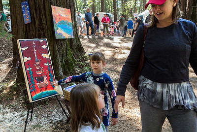 At center, Evie Heinemann, 6, points to a painting by Marna Schindler, that she wants as her mother Emily Heimann and her sister Ellie Heitman, 4, get ready to leave the booth during the King's Mountain Art Fair at the King's Mountain Firehouse in Woodside, Calif., on Monday, September 5, 2016. (LiPo Ching/Bay Area News Group)