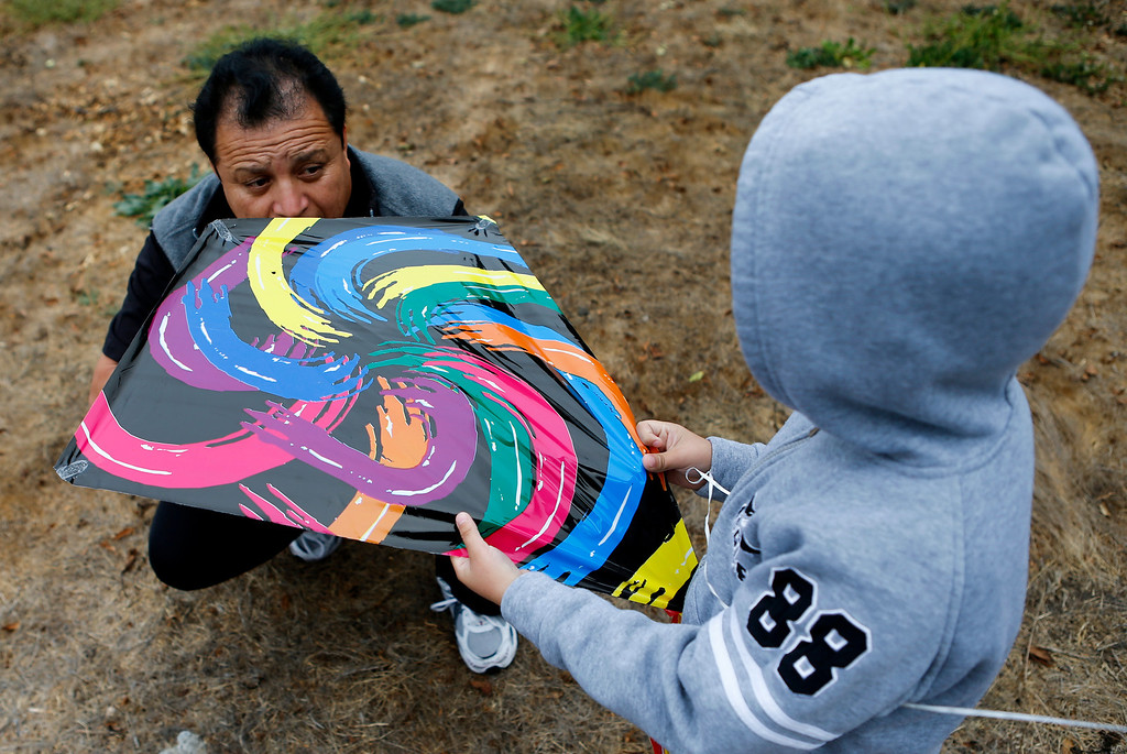 . Eddy Armengo, left, helps son Nareth Pacheco, 8, with his kite at Oyster Point Marina and Park in South San Francisco. (John Green/Bay Area News Group)