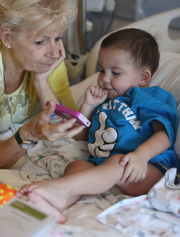 . Joyce Wisecarver, of Antioch, shows her grandson Matthew pictures as he\'s about to be discharged from the UCSF Benioff Children\'s Hospital in San Francisco Calif., on Wednesday, Aug. 14, 2013. Matthew, 2, spent 73 days at UCSF after undergoing a liver/kidney transplant on June 4. (Jane Tyska/Bay Area News Group)