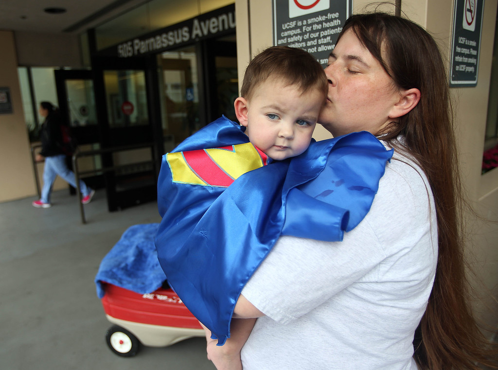 """. Kristi Ouimet, of Antioch, kisses her son Matthew, 2, after he was discharged from the UCSF Benioff Children\'s Hospital in San Francisco Calif., on Wednesday, Aug. 14, 2013. Matthew wore a superhero cape with an \""""M\"""" on the back, one of the many gifts he received while in the hospital. Matthew spent 73 days at UCSF after undergoing a liver/kidney transplant on June 4. (Jane Tyska/Bay Area News Group)"""