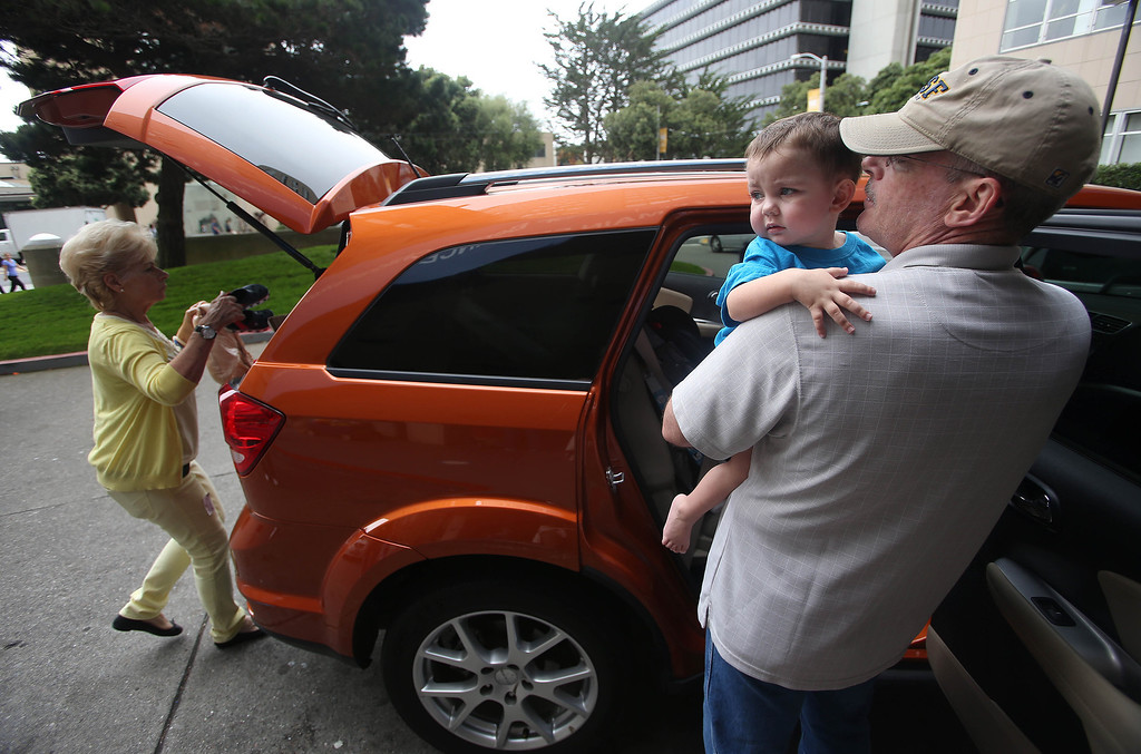 . Kelly Ouimet, of Antioch, leaves with his son Matthew, 2, after he was discharged from the UCSF Benioff Children\'s Hospital in San Francisco Calif., on Wednesday, Aug. 14, 2013. To the left is Matthew\'s grandmother Joyce Wisecarver, of Antioch. Matthew spent 73 days at UCSF after undergoing a liver/kidney transplant on June 4. (Jane Tyska/Bay Area News Group)