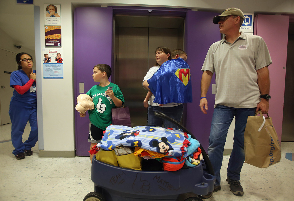 . Kristi Ouimet, center, husband Kelly, right, and son, Patrick, 8, left, of Antioch, wait with her son Matthew, 2, after he was discharged from the UCSF Benioff Children\'s Hospital in San Francisco Calif., on Wednesday, Aug. 14, 2013. To the left is registered nurse Vanessa Nguyen, who came to say goodbye to the family. Matthew spent 73 days at UCSF after undergoing a liver/kidney transplant on June 4. (Jane Tyska/Bay Area News Group)