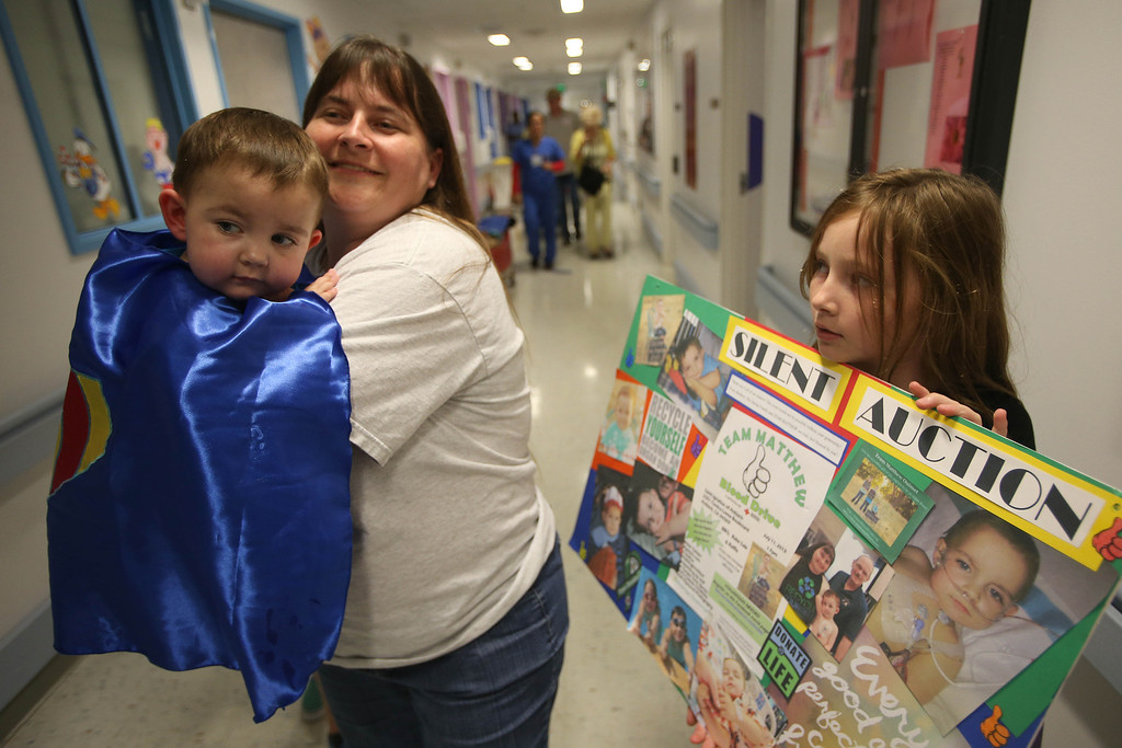 """. Kristi Ouimet, of Antioch, leaves with her son Matthew, 2, after he was discharged from the UCSF Benioff Children\'s Hospital in San Francisco Calif., on Wednesday, Aug. 14, 2013. To the right is her daughter Molly, 10. Matthew wore a superhero cape with an \""""M\"""" on the back, one of the many gifts he received while in the hospital. Matthew spent 73 days at UCSF after undergoing a liver/kidney transplant on June 4. (Jane Tyska/Bay Area News Group)"""