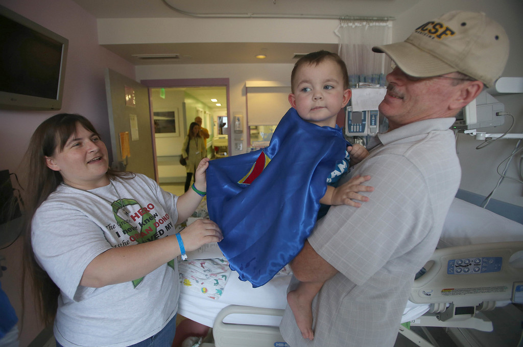 . Kristi Ouimet, of Antioch, and her husband Kelly, right, adjust their son Matthew\'s superhero cape as he\'s discharged from the UCSF Benioff Children\'s Hospital in San Francisco Calif., on Wednesday, Aug. 14, 2013. Matthew, 2, spent 73 days at UCSF after undergoing a liver/kidney transplant on June 4. (Jane Tyska/Bay Area News Group)