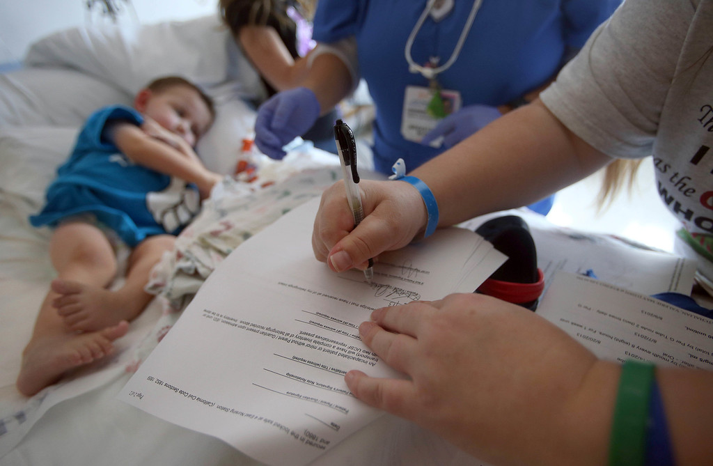 . Kristi Ouimet, of Antioch, signs discharge paperwork for her son Matthew, 2, as they prepare to leave UCSF Benioff Children\'s Hospital in San Francisco Calif., on Wednesday, Aug. 14, 2013. Matthew spent 73 days at UCSF after undergoing a liver/kidney transplant on June 4. (Jane Tyska/Bay Area News Group)