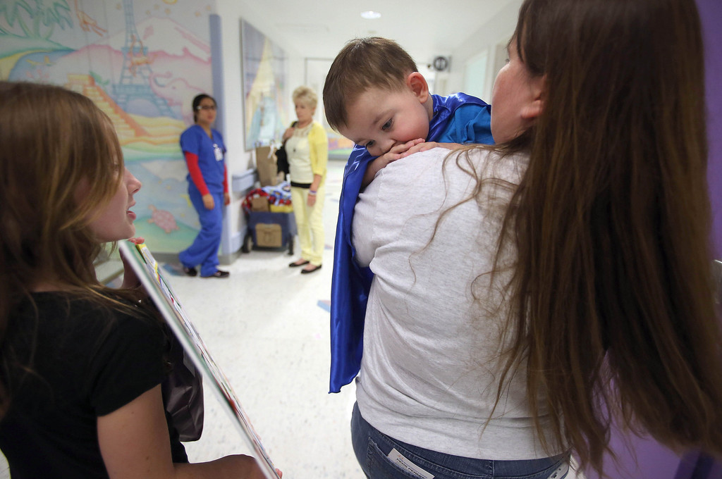 """. Kristi Ouimet, of Antioch, right, leaves with her son Matthew, 2, after he was discharged from the UCSF Benioff Children\'s Hospital in San Francisco Calif., on Wednesday, Aug. 14, 2013. To the left is Kristi\'s daughter Molly Ouimet, 10.  Matthew wore a superhero cape with an \""""M\"""" on the back, one of the many gifts he received while in the hospital. Matthew spent 73 days at UCSF after undergoing a liver/kidney transplant on June 4. (Jane Tyska/Bay Area News Group)"""