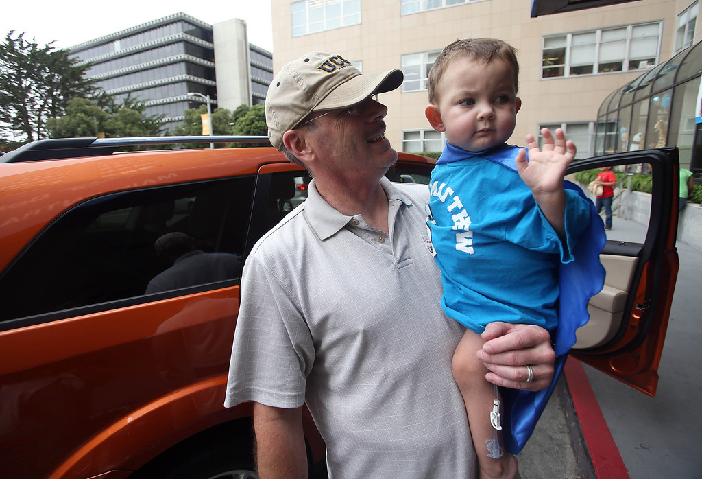 . Kelly Ouimet, of Antioch, holds his son Matthew, 2, as he waves goodbye to hospital personnel after he was discharged from the UCSF Benioff Children\'s Hospital in San Francisco Calif., on Wednesday, Aug. 14, 2013. Matthew spent 73 days at UCSF after undergoing a liver/kidney transplant on June 4. (Jane Tyska/Bay Area News Group)