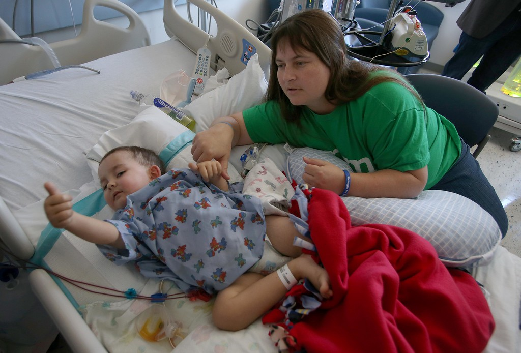 . Kristi Ouimet, of Antioch, comforts her son Matthew, 2, as he gives a thumbs up while recovering from a liver and kidney transplant at UCSF Benioff Children\'s Hospital in San Francisco, Calif., on Wednesday, June 19, 2013.  (Jane Tyska/Bay Area News Group)