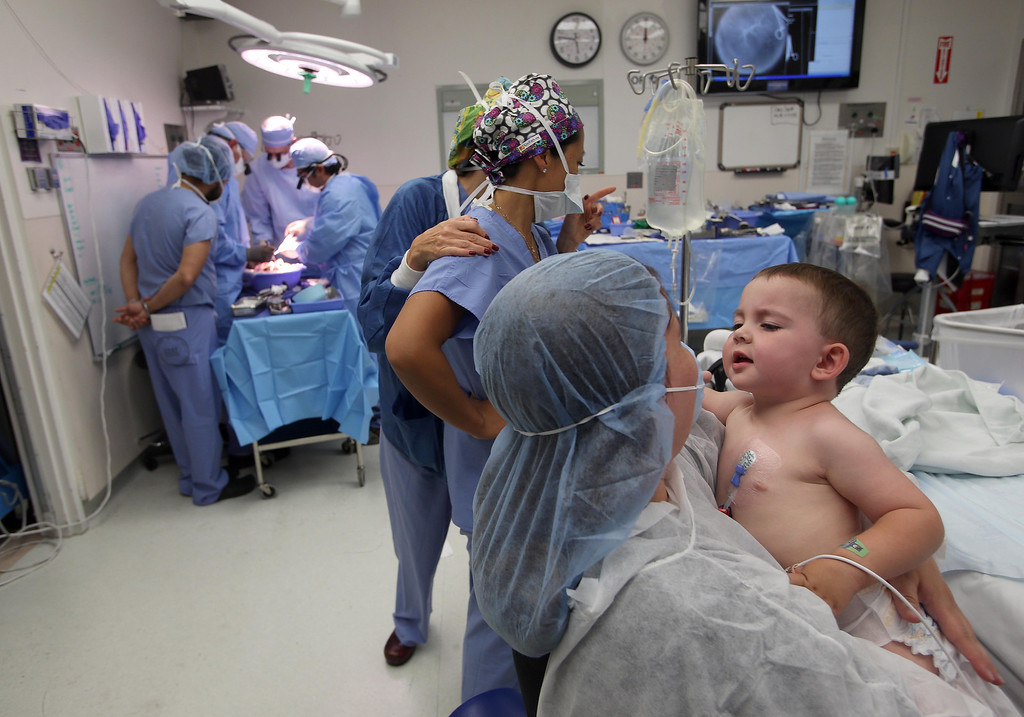 . Kristi Ouimet, of Antioch, spends the last few minutes in the operating room with her son Matthew, 2, before he undergoes anesthesia for a liver and kidney transplant at the UCSF Benioff Children\'s Hospital in San Francisco, Calif., on Tuesday, June 4, 2013. To the left, Dr. John Roberts and his surgical team split a liver. (Jane Tyska/Bay Area News Group)