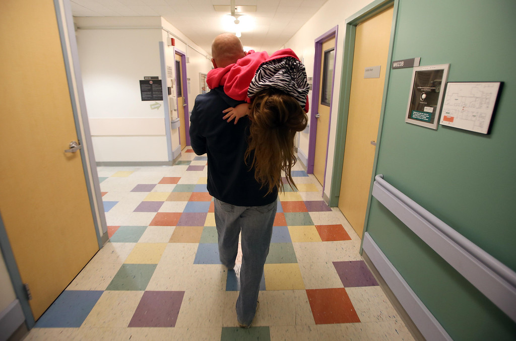 . Jimmy Wisecarver carries his niece Molly Ouimet, 10, to the car as his nephew and her brother Matthew, 2, undergoes a liver and kidney transplant at the UCSF Benioff Children\'s Hospital in San Francisco, Calif., on Wednesday, June 5, 2013.  (Jane Tyska/Bay Area News Group)