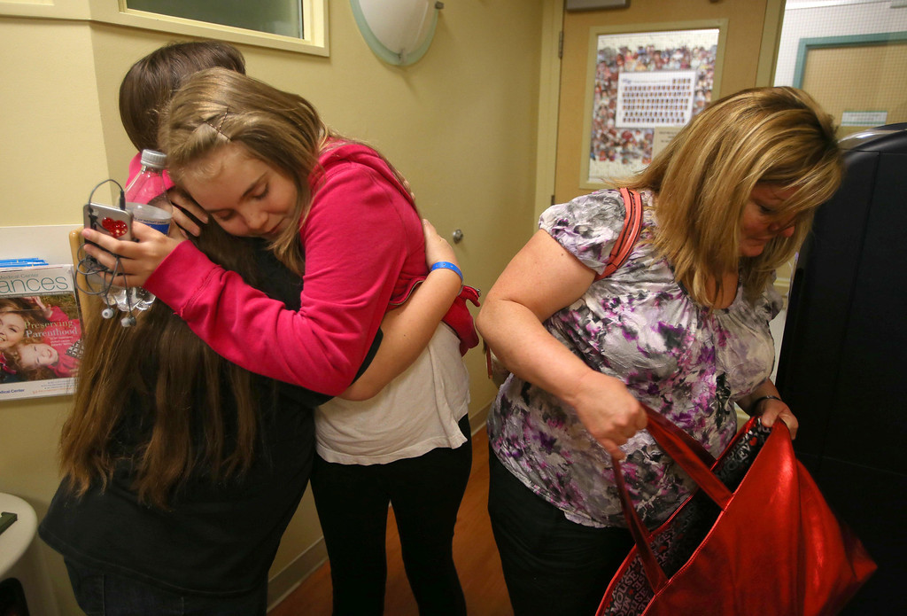 . Kristi Ouimet, of Antioch, hugs friend Alyssa Welch, 16, of Riverbank, Calif., as Ouimet\'s son Matthew, 2,  undergoes a liver and kidney transplant at the UCSF Benioff Children\'s Hospital in San Francisco, Calif., on Wednesday, June 5, 2013. To the right is Alyssa\'s mom Kim Welch. Alyssa met Matthew while doing dialysis at UCSF and recently had a double transplant herself.  (Jane Tyska/Bay Area News Group)