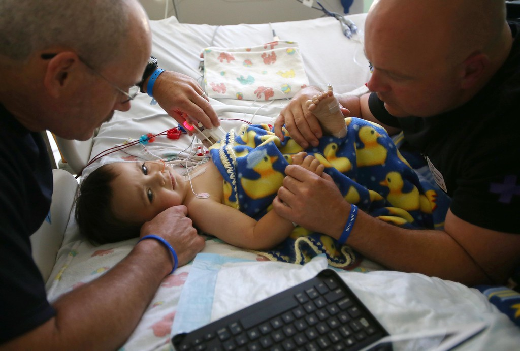 . Kelly Ouimet, of Antioch, left, comforts his son Matthew, 2, along with Matthew\'s uncle Jimmy Wisecarver, right, of Brentwood, in the ICU after Matthew had follow up surgery at UCSF Benioff Children�s Hospital in San Francisco, Calif., on Wednesday, June 12,  2013. Matthew had his initial incision closed and a feeding tube inserted. Doctors took a biopsy from his organs to make sure their was no sign of rejection, and results were good.  Matthew had a liver and kidney transplant at UCSF on June 4.  (Jane Tyska/Bay Area News Group)