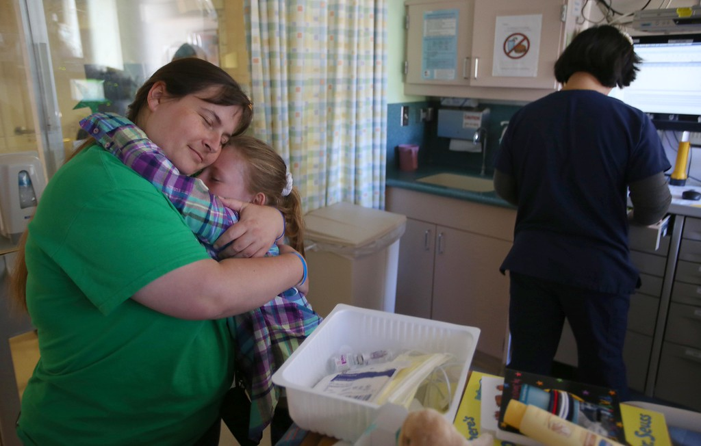 . Kristi Ouimet, of Antioch, embraces her daughter Molly, 10, as her son Matthew, 2, recovers in the ICU after Matthew had follow up surgery at UCSF Benioff Children�s Hospital in San Francisco, Calif., on Wednesday, June 12,  2013.  (Jane Tyska/Bay Area News Group)