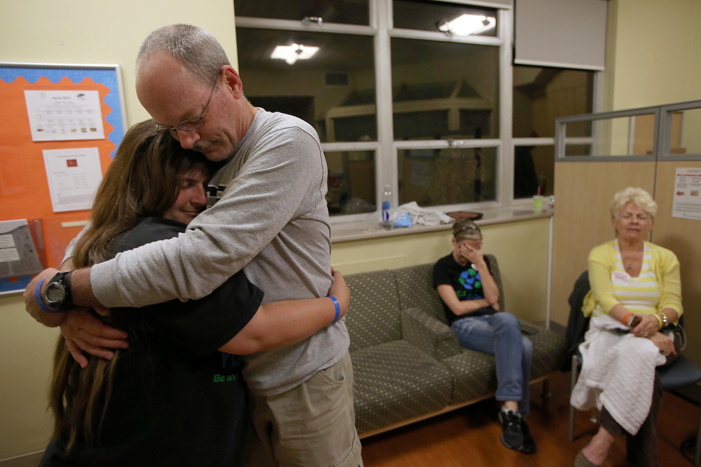 """. Kristi and Kelly Ouimet, of Antioch, embrace after receiving news from Dr. Peter Stock that their son Matthew, 2, is \""""doing great\"""" as he undergoes a liver and kidney transplant at the UCSF Benioff Children\'s Hospital in San Francisco, Calif., on Wednesday, June 5, 2013. To the right is family friend Kim Wiley, of Lincoln, Calif., and Kristi\'s mom Joyce Wisecarver, of Antioch, both cry at the good news. Stock oversaw the kidney portion of the transplant.  (Jane Tyska/Bay Area News Group)"""