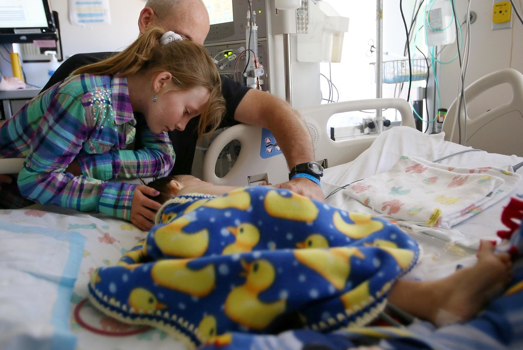 . Kelly Ouimet, of Antioch, and his daughter Molly, 10, comforts his son and her brother Matthew, 2, in the ICU after Matthew had follow up surgery at UCSF Benioff Children�s Hospital in San Francisco, Calif., on Wednesday, June 12,  2013.  (Jane Tyska/Bay Area News Group)
