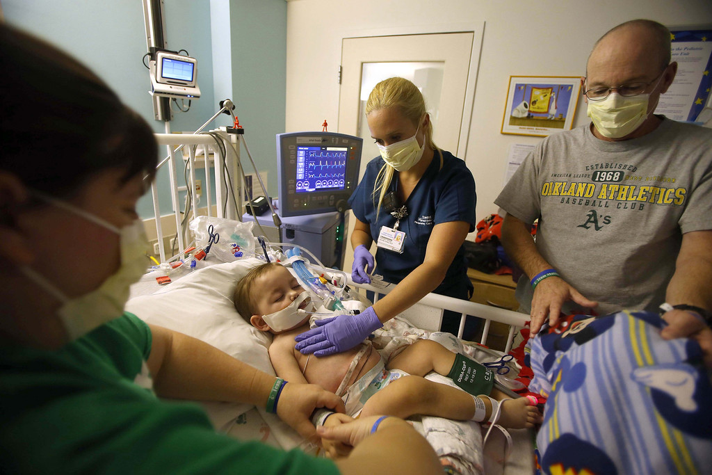 . Respiratory care practitioner Jennifer Willey, center, attends to Matthew Ouimet, 2, of Antioch, as he\'s comforted by his parents Kristi, left, and Kelly Ouimet as he recovers from a recent surgery in the pediatric ICU at UCSF Benioff Children\'s Hospital in San Francisco, Calif., on Friday, July 5, 2013. Matthew received a liver/kidney transplant at UCSF on June 4, and has had some post-surgery complications. He underwent surgery on July 3 to repair a leaking bile duct on his liver, and has been fighting a virus that has affected his breathing. Matthew was intubated to help his breathing and give his body time to rest and heal. (Jane Tyska/Bay Area News Group)