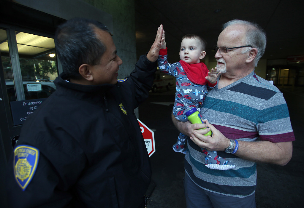 ". Security guard Mel Velasco, left, gives a high five to Matthew Ouimet, 23 months, of Antioch, at UCSF Benioff Children\'s Hospital in San Francisco, Calif., on Tuesday, Jan. 22, 2013. To the right is Matthew\'s grandfather Jim Wisecarver, also of Antioch.""He\'s my inspiration,\"" Velasco said. \""I always pray for my buddy.\"" Matthew is still awaiting both a liver and kidney transplant and does hemodialysis at UCSF Medical Center six times per week. (Jane Tyska/Staff)"