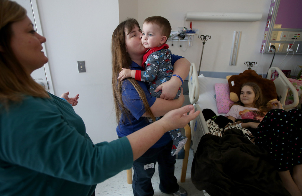. Kristi Ouimet, of Antioch, center, kisses her son Matthew, 23 months, at UCSF Benioff Children\'s Hospital in San Francisco, Calif., on Tuesday, Jan. 22, 2013. To the left is friend Kim Welch, of Riverbank, Calif. Welch\'s daughter, Alyssa, 15, right, received a liver and kidney transplant on Jan. 15 and is doing well after surgery. Matthew is still awaiting both a liver and kidney transplant and does hemodialysis at UCSF Medical Center six times per week. (Jane Tyska/Staff)