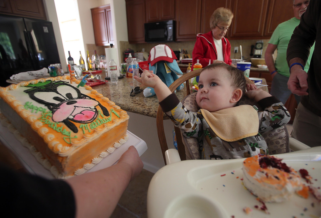 . Kristi Ouimet, left, brings her son Matthew, 2, a cake made by his grandmother Joyce Wisecarver, as they celebrate his birthday with family and friends at their home in Antioch, Calif., on Sunday, Feb. 10, 2013. Matthew, who suffers from primary hyperoxaluria type 1, a rare liver disease, turned two on Feb. 11. He undergoes dialysis six times a week at the UCSF Medical Center in San Francisco, and is on the transplant list awaiting a liver and kidneys. (Jane Tyska/Staff)