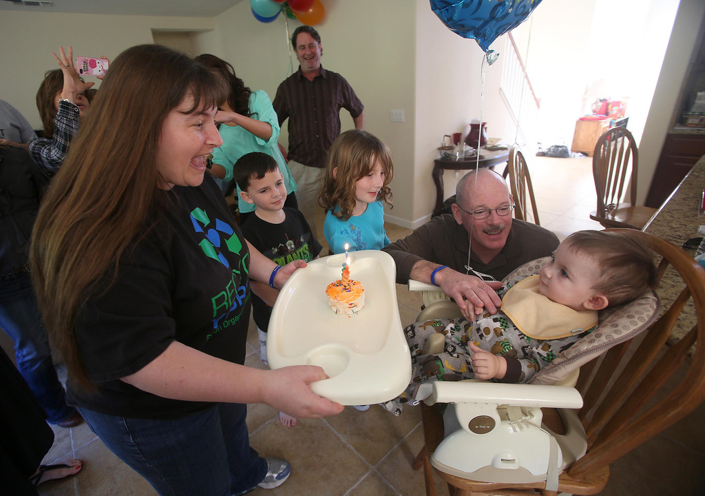 . Kristi Ouimet, left, brings her son Matthew, 2, a cupcake as she celebrates his birthday with family and friends at their home in Antioch, Calif., on Sunday, Feb. 10, 2013. To the right is her son Patrick, 7, daughter Molly, 10, and husband Kelly Ouimet. Matthew, who suffers from primary hyperoxaluria type 1, a rare liver disease, turned two on Feb. 11. He undergoes dialysis six times a week at the UCSF Medical Center in San Francisco, and is on the transplant list awaiting a liver and kidneys. (Jane Tyska/Staff)