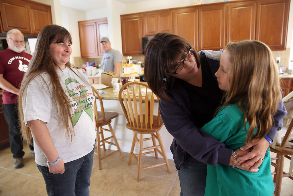 . Maggie, center, who preferred not to give her last name, hugs Molly Ouimet, 10, right, as they meet for the first time at the Ouimet\'s home in Antioch, Calif., on Friday, Oct. 25, 2013. To the left is Molly\'s mom Kristi Ouimet, her dad Jim Wisecarver, of Antioch, far left, and brother Jimmy Wisecarver, of Brentwood, center. Maggie\'s son Brandon, 22, died in a car accident and was the donor for Kristi and Kelly Ouimet\'s son Matthew, 2, when he received a liver and kidney transplant at the UCSF Benioff Children\'s Hospital in San Francisco on June 4-5. This was the first time Maggie had met the Ouimet family after recently corresponding on Facebook and through text messages. (Jane Tyska//Bay Area News Group)
