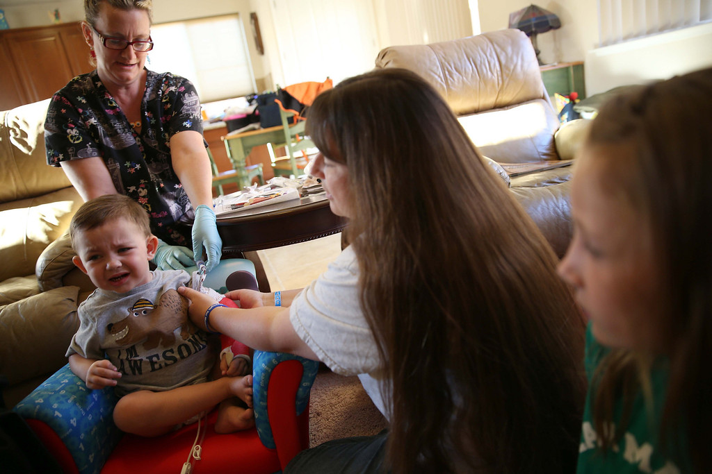 . Matthew Ouimet, 2, has blood drawn by Kaiser home health nurse Rosie Turner, left, rear, as his mom Kristi Ouimet, center, consoles him at the Ouimet\'s home in Antioch, Calif., on Friday, Oct. 25, 2013. To the right is Matthew\'s sister Molly, 10. Kristi and her husband Kelly Ouimet met Maggie, who preferred not to give her last name, after her son Brandon, 22, died in a car accident and was Matthew\'s donor when he received a liver and kidney transplant at the UCSF Benioff Children\'s Hospital in San Francisco on June 4-5. This was the first time Maggie had met the Ouimet family after recently corresponding on Facebook and through text messages. (Jane Tyska//Bay Area News Group)