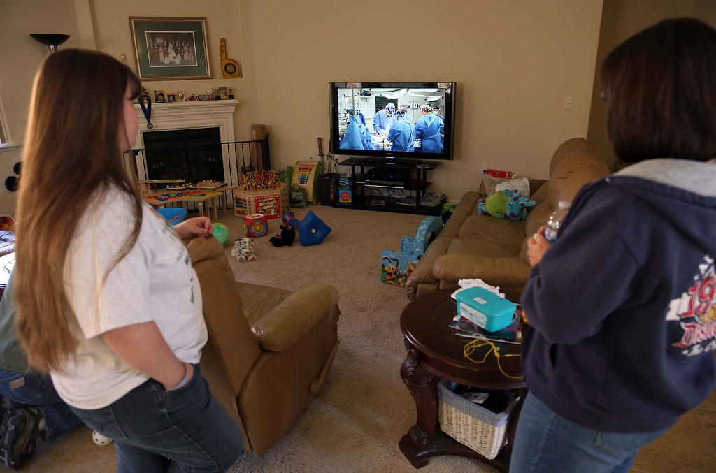 . Kristi Ouimet, left, and Maggie,  right,who preferred not to give her last name, watch a video of Kristi\'s son Matthew\'s liver and kidney transplant at the Ouimet\'s home in Antioch, Calif., on Friday, Oct. 25, 2013. Maggie\'s son Brandon, 22, died in a car accident and was the donor for Kristi and Kelly Ouimet\'s son Matthew, 2, when he received a liver and kidney transplant at the UCSF Benioff Children\'s Hospital in San Francisco on June 4-5. This was the first time Maggie had met the Ouimet family after recently corresponding on Facebook and through text messages. (Jane Tyska//Bay Area News Group)
