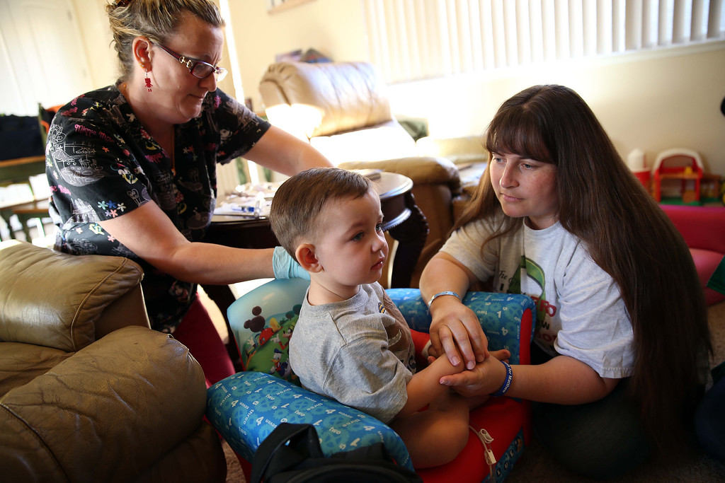 . Matthew Ouimet, 2, is comforted by his mom Kristi Ouimet, right, as he has blood drawn by Kaiser home health nurse Rosie Turner, left, at the Ouimet\'s home in Antioch, Calif., on Friday, Oct. 25, 2013. Kristi and her husband Kelly Ouimet met Maggie, who preferred not to give her last name, after her son Brandon, 22, died in a car accident and was Matthew\'s donor when he received a liver and kidney transplant at the UCSF Benioff Children\'s Hospital in San Francisco on June 4-5. This was the first time Maggie had met the Ouimet family after recently corresponding on Facebook and through text messages. (Jane Tyska//Bay Area News Group)