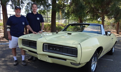 Mike Natali, left, and Chris Patterson of Danville show the 1968 Pontiac GTO convertible they drove across he country.   (Photo by David Krumboltz)
