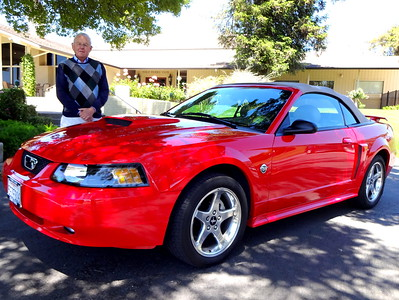 Auto dealer Buzz Landis shows the 2004 Ford Mustang convertible.   (Photo by David Krumboltz)