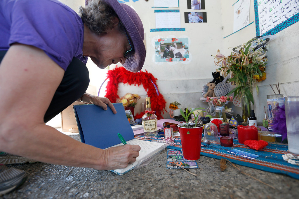 ". Rebecca Tarver, of Oakland, signs a remembrance book for ""Willie\"" at a memorial for him at Lake Merritt in Oakland, Calif., on Tuesday, Aug. 30, 2016. (Jane Tyska/Bay Area News Group)"